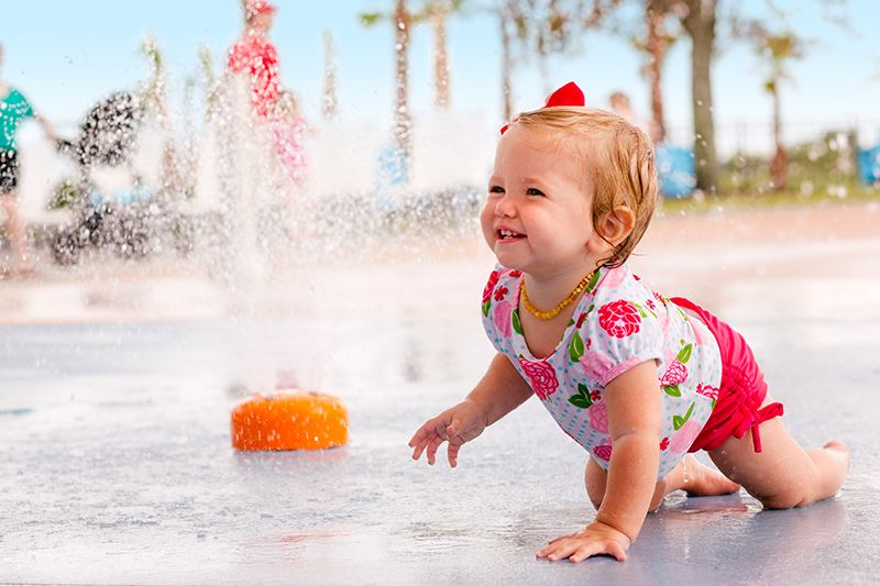 Toddler in splash pad area in Waterset.