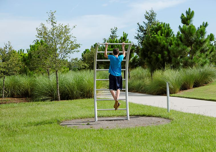 Man on pull up bars on fitness trail in Waterset