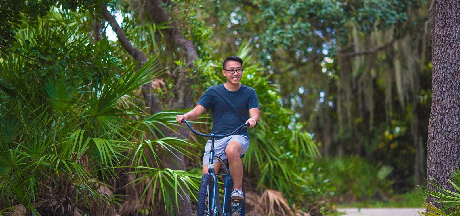 Man riding bicycle on wooded boardwalk trail in Waterset.