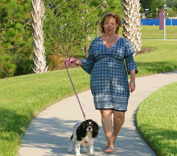 Woman walking along a trail with her dog.
